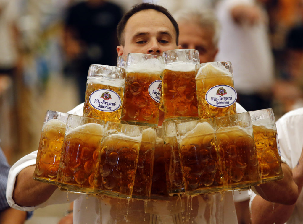 German Oliver Struempfl competes to set a new world record in carrying one liter beer mugs over a distance of 40 m (131 ft 3 in) in Abensberg September 7, 2014. Struempfl carried 27 mugs over 40 meters to set a new record for the Guinness book of records. REUTERS/Michael Dalder (GERMANY - Tags: SOCIETY TPX IMAGES OF THE DAY) - RTR459HQ